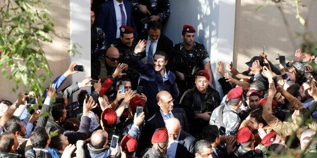 Saad al-Hariri, who suspended his decision to resign as prime minister, gestures to his supporters at...
