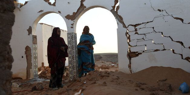 Sahrawi refugee women (L) stand at their house which was destroyed during heavy rain last year at the...