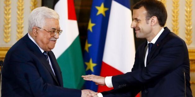 French President Emmanuel Macron (R) shakes hands with Palestinian President Mahmud Abbas at the end...