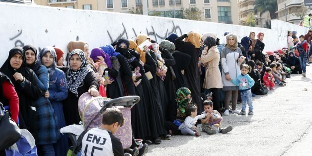 Syrian refugees queue to receive aid consisting of winter clothing, blankets, heaters and other necessities,...
