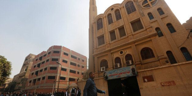 Policemen inspect the site of attack on Mar Mina church in Helwan district on the outskirts of Cairo,...