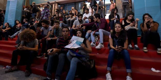 Tunisian youths check the programme as they wait outside a movie theatre during the Carthage Film Festival...