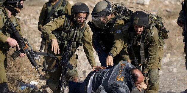 Israeli soldiers detain a Palestinian protester during clashes following a protest against Jewish settlements,...