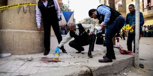 TOPSHOT - Egyptian security members and forensic police inspect the site of a gun attack outside a church...