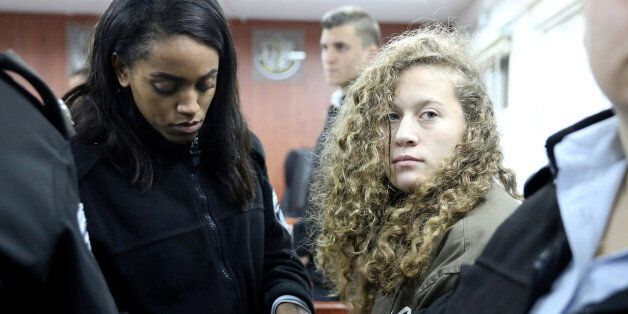 Palestinian teen Ahed Tamimi (R) enters a military courtroom escorted by Israeli Prison Service personnel...