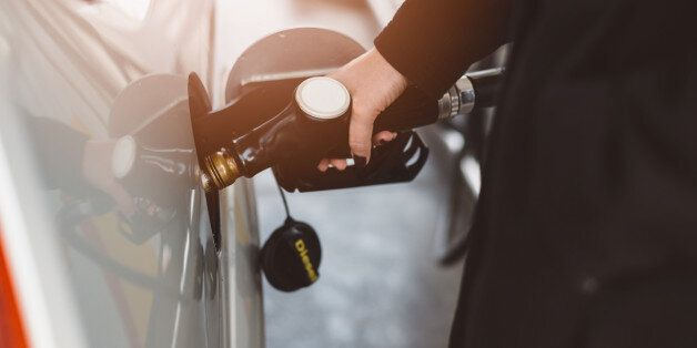 Woman refueling car with diesel at the gas