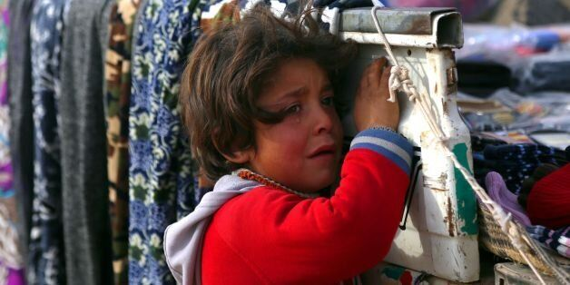 A displaced Syrian child, who was forced to leave his hometown by the war against the Islamic State (IS)...