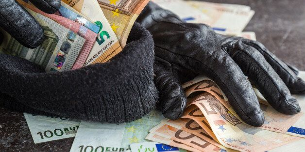 Quick loot in the store. Thief' s hands in black leather gloves stealing a money and putting it in the...