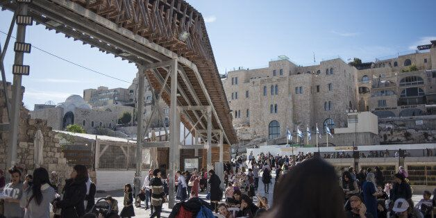 Tourists and locals pass a walkway to Temple Mount running through the Western Wall in Jerusalem, Israel,...
