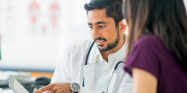 A doctor is talking to a patient about her condition at her