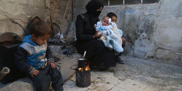DAMASCUS, SYRIA - DECEMBER 28: A woman holds Syrian baby Karim, who lost his left eye and his mother...