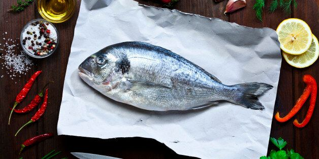Top view of a raw sea bream fish on paper at the center of an horizontal frame with cooking and seasoning...