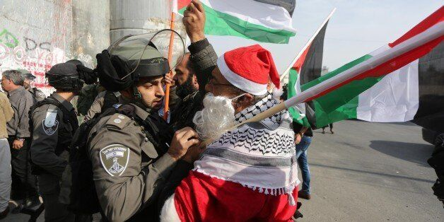 BETHLEHEM, WEST BANK - DECEMBER 23 : Israeli security forces intervene protesters dressed up as Santa-Claus...