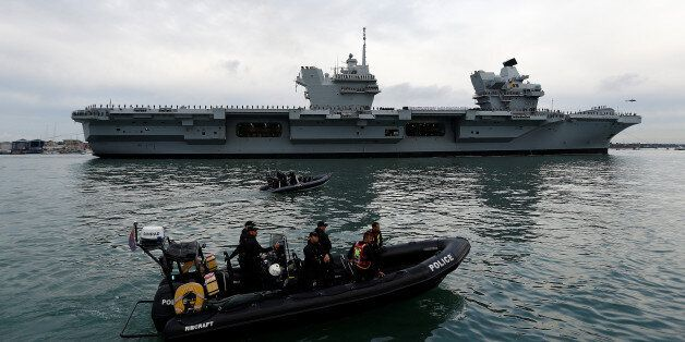 Police officers stand guard in a rigid inflatable boat (RIB) as the Royal Navy's new aircraft carrier...