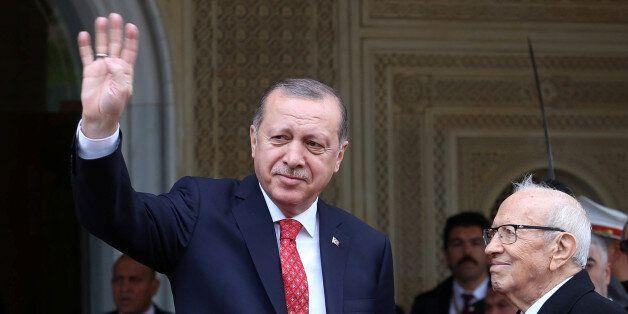 Turkey's President Tayyip Erdogan gestures to photographers at Carthage Palace in Tunis, Tunisia, December...