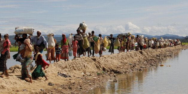Rohingya refugees, who crossed the border from Myanmar two days before, walk after they received permission...