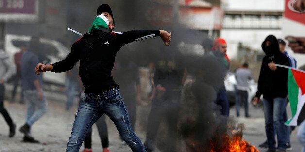 A Palestinian demonstrator hurls a stones towards Israeli troops during clashes at a protest as Palestinians...