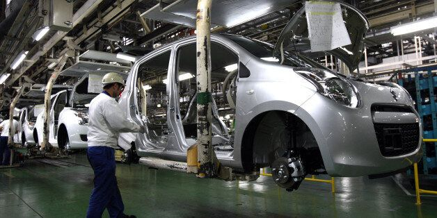 An employee works near a Suzuki Motor Corp. Swift vehicle on the assembly line at the company's Kosai...