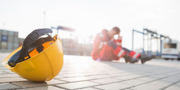 Yellow hardhat at shipyard with depressed male worker in
