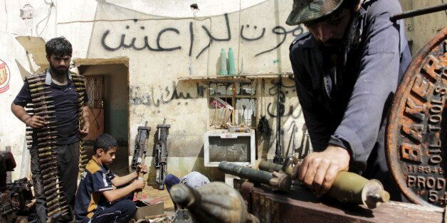 Iraqi volunteers fix the weapons of the Hashid Shaabi militia, at a shop on the outskirts of Basra June...