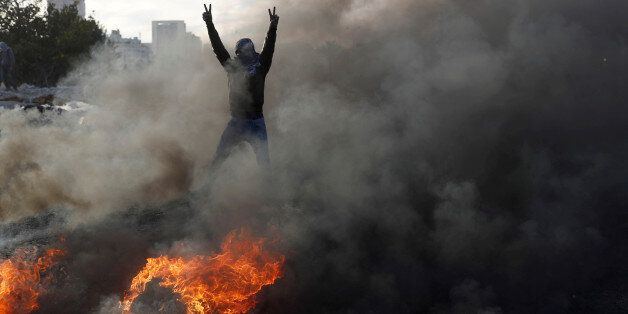 A masked Palestinian gestures in front of a burned barricade during a protest against U.S. President...