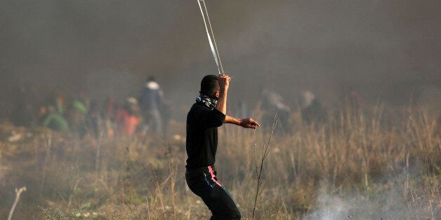 Palestinian protesters hurl stones towards Israeli troops during clashes following a protest against...