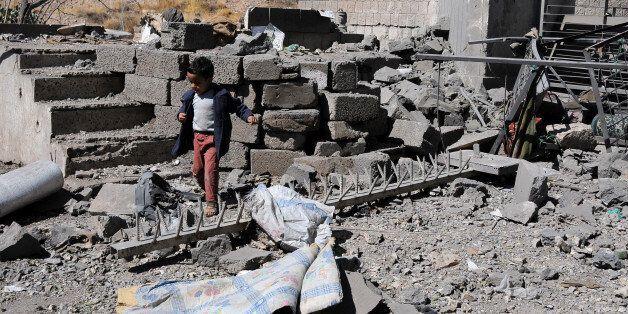 SANA'A, YEMEN – DECEMBER 09: A boy walks on rubble of Yemen's State Satellite Television Station...