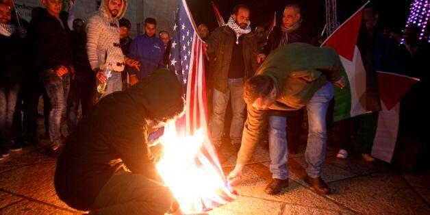 Palestinian demonstrators burn the US flag in Bethlehem's Manger Square in protest to the declaration...