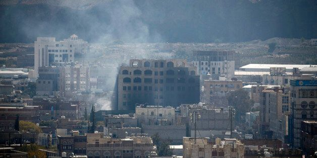 Smoke billows behind a building in the Yemeni capital Sanaa on December 3, 2017, during clashes between...