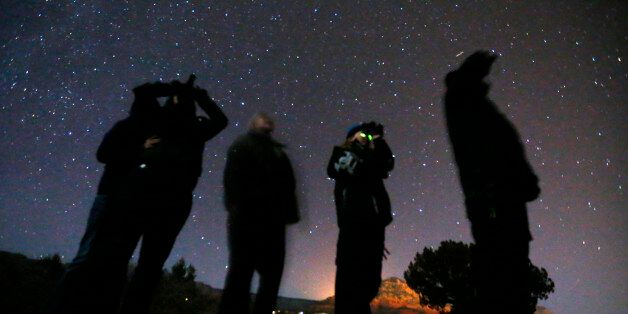People use night vision goggles to look at the night sky during an Unidentified Flying Object (UFO) tour...