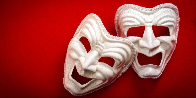 Comedy and Tragedy theatrical mask isolated on a red background and copy