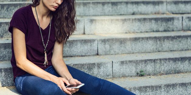 Sad girl looking at the telephone and sitting on stairs outside. Creative crop – no