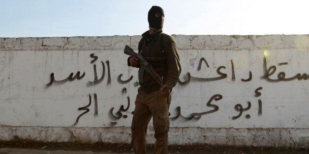 A Free Syrian Army fighter carries his weapon as he stands in front of graffiti that