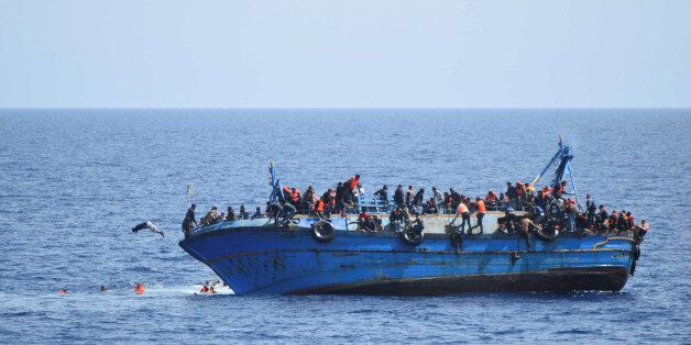 Migrants are seen on a capsizing boat before a rescue operation by Italian navy
