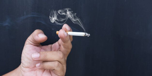 Close up cigarette or tobacco with smoke in hand and copy