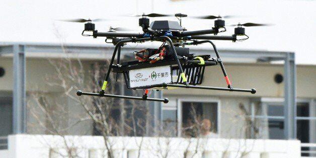 A drone developed by Japan's Autonomous Control Systems Laboratory (ACSL) flies beside a condomimium...