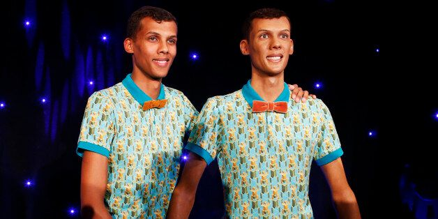 Belgian singer Stromae stands next to his figure at the Grevin wax museum during the presentation of...