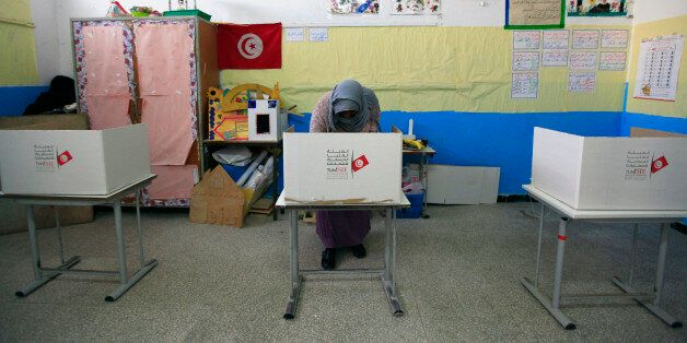 A Tunisian woman casts her ballot in the capital Tunis December 21, 2014. Tunisians began voting on Sunday...