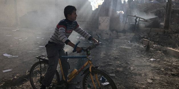 A Palestinian boy rides a bicycle near a militant target that was hit in an Israeli airstrike in the...