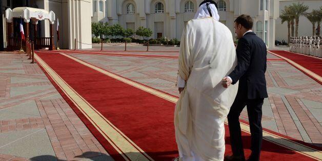 French President Emmanuel Macron (R) walks alongside Qatari Emir Sheikh Tamim bin Hamad al-Thani during...