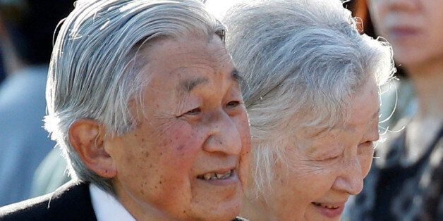 Japan's Emperor Akihito (L), flanked by Empress Michiko, greets guests during the annual autumn garden...