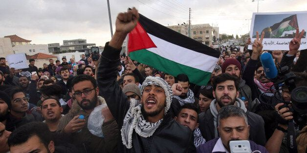 Protesters shout slogans and wave the Jordanian flag during a protest near the American Embassy in Amman...