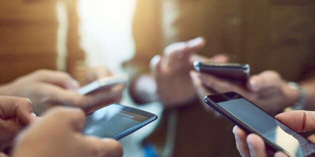 Cropped shot of a group of colleagues using their smart phones in