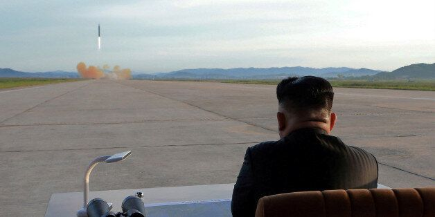 North Korean leader Kim Jong Un watches the launch of a Hwasong-12 missile in this undated photo released...