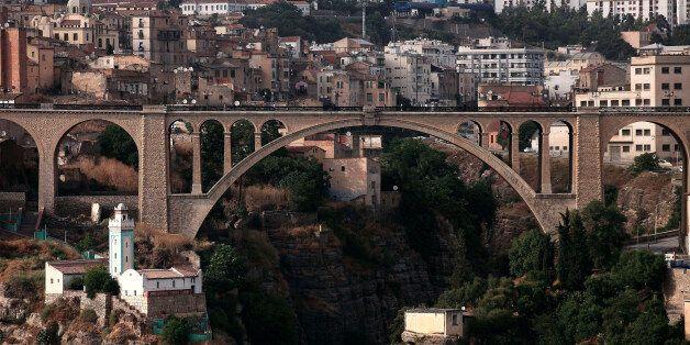 People cross over a bridge in the eastern city of Constantine June 21, 2012. REUTERS/Zohra Bensemra (ALGERIA...