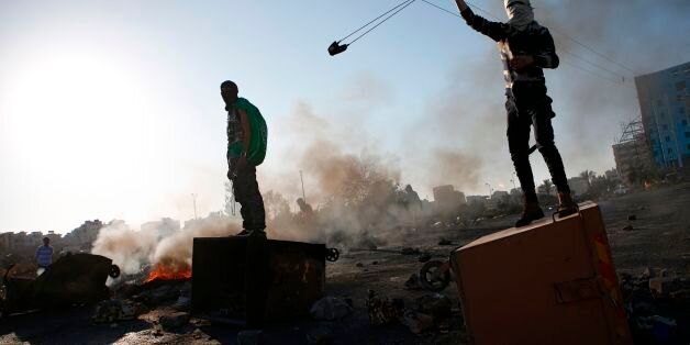 TOPSHOT - A Palestinian protestor uses a slingshot during clashes with Israeli forces near an Israeli...