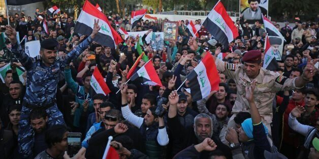Iraqis wave their national flag in Baghdad's Tahrir Square on December 10, 2017, during a gathering celebrating...