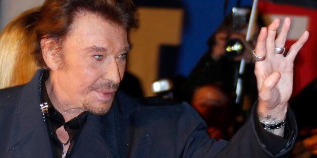 French singer Johnny Hallyday waves as he arrives at the Cannes festival palace to attend the NRJ Music...