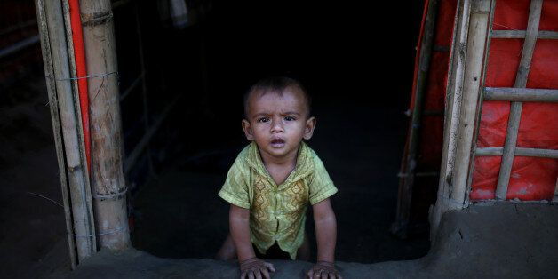 A Rohingya refugee baby sits at the entrance of his family's temporary shelter at the Onchiprang refugee...