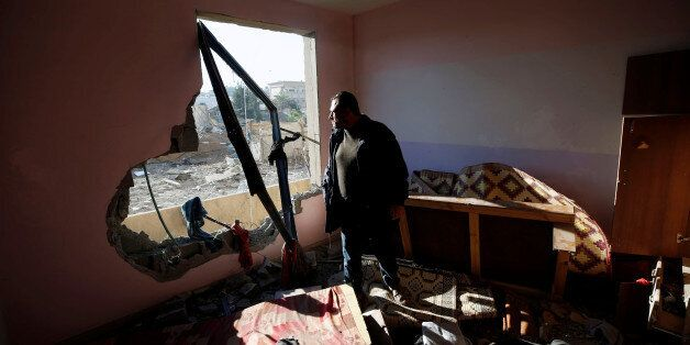 A Palestinian man looks out of his apartment that was damaged in an Israeli airstrike at a nearby militant...